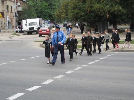Сотрудник ГАИ переводит школьников через дорогу